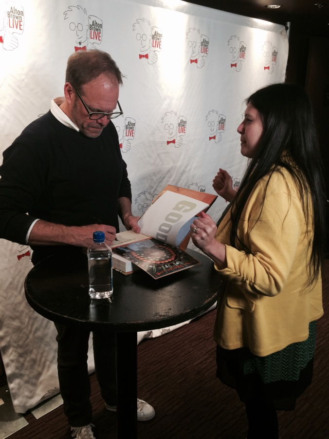 Alton Brown signs my copy of his book while answering my question about brining!