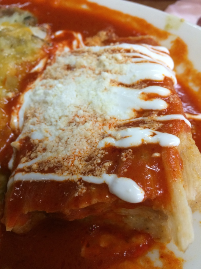 A homemade chicken tamale smothered in salsa rojo, crema and cotija cheese.